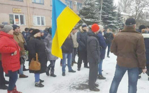 After walking out of work Feb. 14, coal miners in Donetsk region of Ukraine, joined by family members, protest at company headquarters during strike demanding payment of back wages.