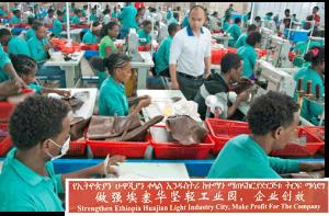 """Fábrica de zapatos Huajian de propiedad china en Addis Ababa, Etiopía. Recuadro, cartel en la fábrica dice: """"Fortalezca industria ligera Huajian en Etiopía. Produzca ganancias para la compañía""""."""