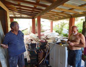 """Electricista Raúl Laboy (izq.) y Wilfredo Abreu, en Humacao, Puerto Rico, en un descanso de su labor de reconstrucción. """"El huracán social"""" del capitalismo es peor que el natural, dijo Laboy."""