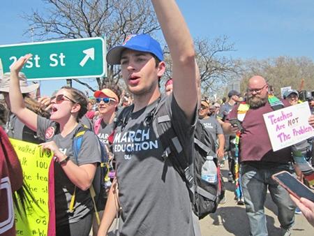 """Maestros huelguistas y sus partidarios al final de marcha de 110 millas desde Tulsa al capitolio en Oklahoma City son recibidos por miles que coreaban, """"Estamos orgullosos de ustedes""""."""