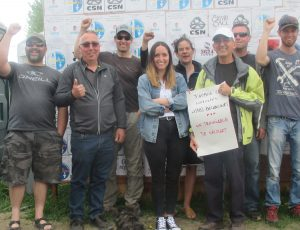 United Steelworkers members locked out by ABI Bécancour bosses in Quebec picket plant May 27, in front of solidarity wall. Walmart worker Michel Prairie holds poster of support.