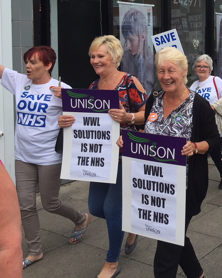 Hospital workers march in Wigan, England, June 9 during 48-hour strike over jobs transfer, new two-tier pay.
