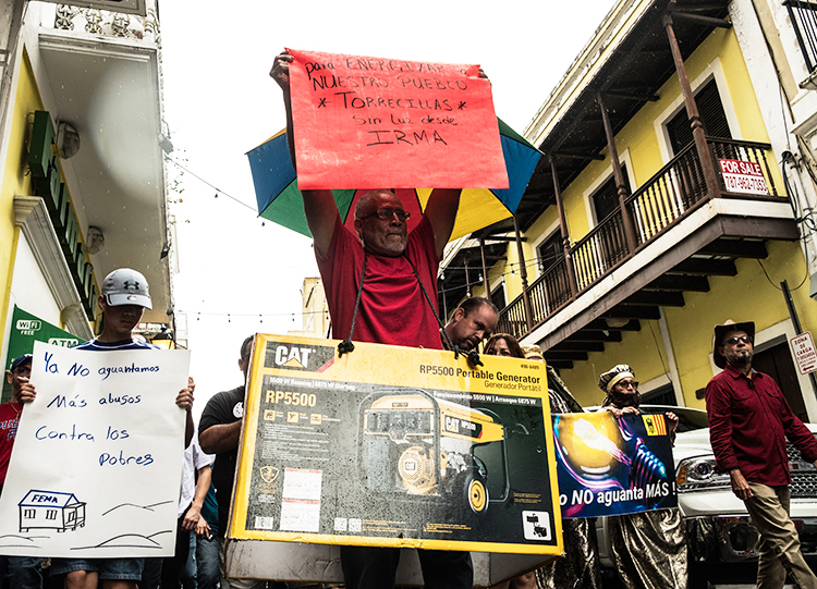 "San Juan protest Jan. 20. Sign carried by man in middle says, ""Energize our town Torrecillas. Without light since Irma."" Sign at left says, ""We can't take any more abuses against the poor."""