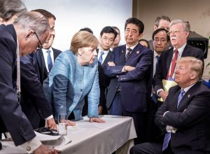 Donald Trump, Angela Merkel and other capitalist rulers stand off during G-7 summit June 9. Tensions are product of crisis of capitalism, which sharpens competition between rivals.