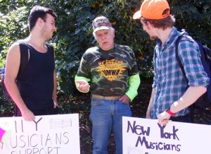 Dennis Bugash, center, from central Pennsylvania with 25 years in coal mines, talks to musicians Dean Mahoney, left, and Harry D'Agostino, at Columbus, Ohio, pension rally July 12.