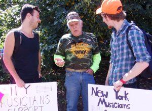 Dennis Bugash (centro), minero por 25 años, de Pennsylvania, habla con músicos Dean Mahoney (izq.), y Harry D'Agostino, en acto por pensiones en Columbus, Ohio, el 12 de julio.