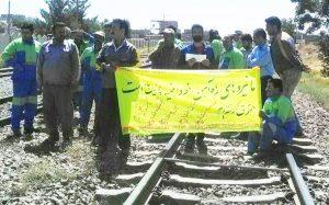 """Trabajadores de vías cerca de Nayshabour, el 7 de agosto, protestan efectos de las guerras contrarrevolucionarias de gobernantes iraníes en la región. Pancarta dice, """"No nos han pagado por meses. No tenemos seguridad. No tenemos futuro. No tenemos honor. No tenemos pan. No tenemos beneficios sociales""""."""