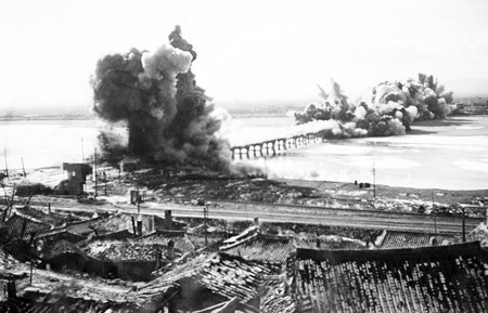 U.S.-organized United Nations forces destroy bridge near Hamhung, North Korea, to prevent its use, Dec. 19, 1950. Imperialist troops were driven back by DPRK forces and Chinese volunteers. Washington used its massive airpower to destroy virtually every building in the North.