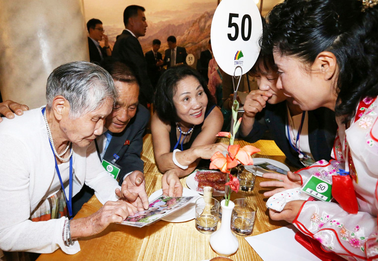 As part of first reunion in years Aug. 20, South Korean Lee Keum-seom, 92, left, looks at photo with son Ri Sang Chol, who lives in the North. They hadn't seen each other since Korean War.