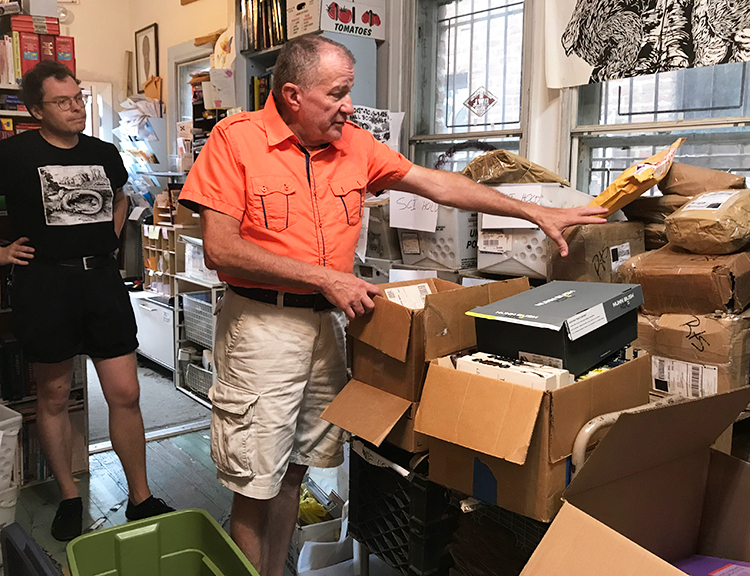 Tom Haney, right, with Philadelphia-based Books Through Bars, points to stacks of books returned by prison authorities because of new rules restricting prisoners' right to receive them.