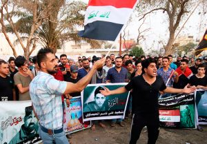 Demonstrators Sept. 12 in Basra hold Iraqi flags and images of protesters killed at previous actions demanding water, electricity, jobs and an end to Iranian interference in the country.