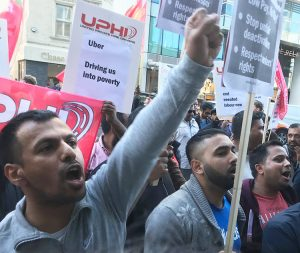 Uber workers in London march around company office Oct. 9 during 24-hour strike, demanding drivers be treated as workers, not contractors, with improved pay and right to join a union.