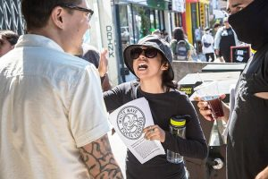 """Demonstration against Weird Wave Coffee shop. Leaflet says, """"White wave. Get out, sellouts."""""""