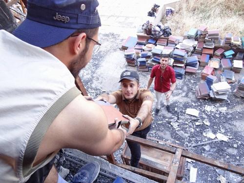 Voluntarios rescatan libros de la biblioteca de la Universidad de Mosul, la cual fue incendiada por el Estado Islámico.