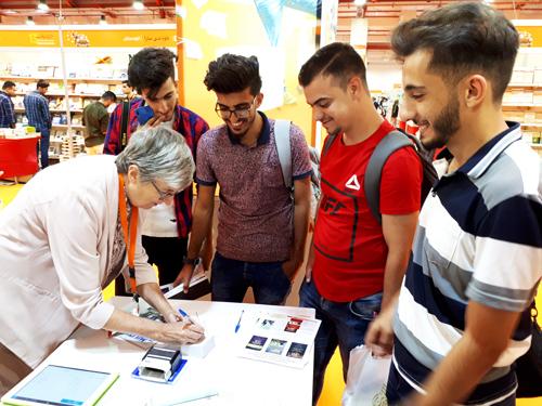 Munaf Ghanim, Mohammad Khalid Aswad, Safwan Al Madany y Saad Salim, voluntarios del festival de libros de Mosul visitan el stand de Pathfinder en la Feria Internacional del Libro de Erbil.