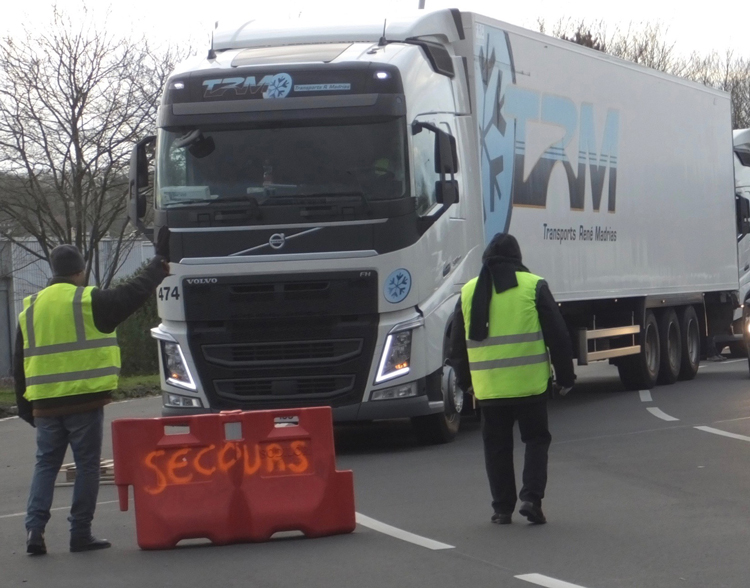 "Yellow vest protesters stop truck Dec. 11 in Dieppe, a coastal town in Normandy region of northern France. Cars and buses were allowed to pass. ""Macron thinks those who labor are dumb,"" protester Nathalie Girard told U.K. Communist League member Debra Jacobs, ""but the opposite is the case. The work we do — that's intelligence, that's creativity."""