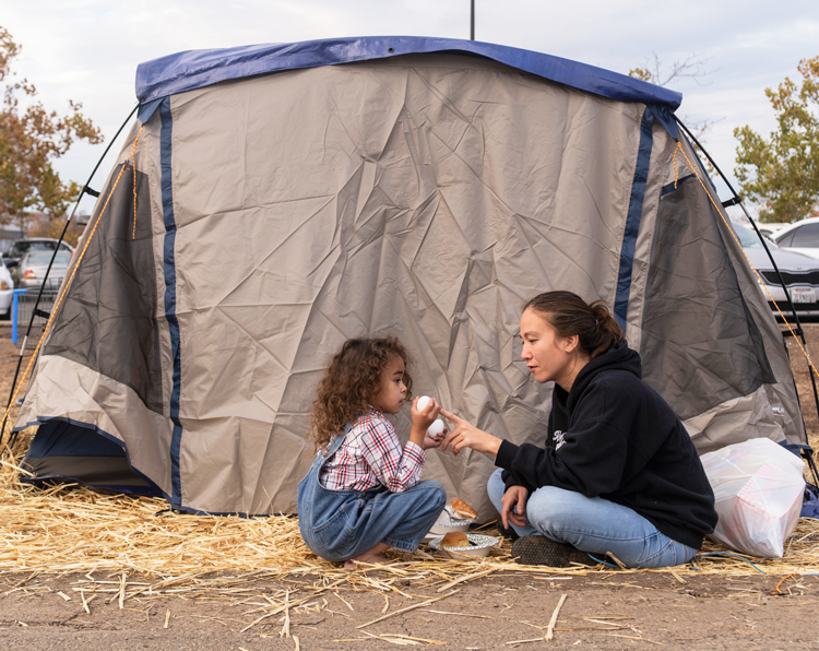 Fire survivors Rubyjade Stewart and son Rene, outside their tent in Chico Walmart lot Nov. 21.