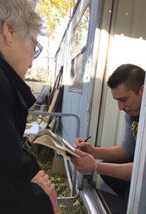 """Miembro del PST Helen Meyers con Ramón Cuellar en su trailer en Roseville, Minnesota, 21 de octubre. """"Tengo que hacer dos trabajos"""", dijo. """"Apoyo lo que están haciendo"""". Cuellar compró una suscripción al Militante y el libro El historial antiobrero de los Clinton."""
