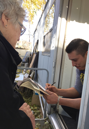 "Socialist Workers Party member Helen Meyers speaks with Ramón Cuellar at his trailer in Roseville, Minnesota, Oct. 21, as he signs up for subscription to Militant. ""I have to work two jobs,"" he said. ""I'm all for what you are doing."" He also got a copy of The Clintons' Anti-Working-Class Record."