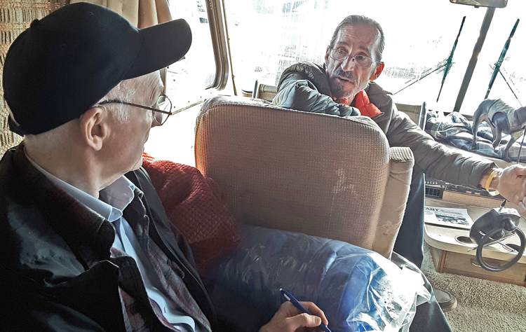 """SWP member Joel Britton, left, talks with carpenter Tony Worino in his RV at fire refugee center in Chico, Calif. """"How do the rich control everything and manipulate us?"""" Worino asked."""