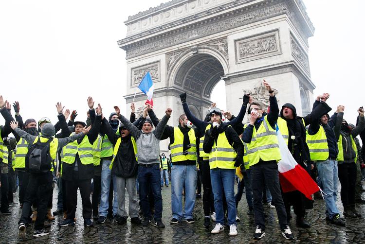 Manifestantes en Arco del Triunfo en París, 1 de diciembre, antes de ser atacados por la policía.