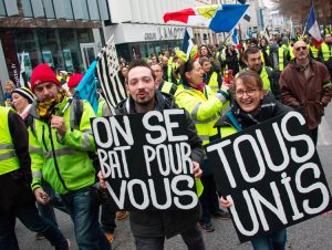 """Yellow vest protesters march in Rennes, France, Dec. 29. """"We fight for you,"""" sign on left says. Protesters continue pressing for further concessions from the French government."""