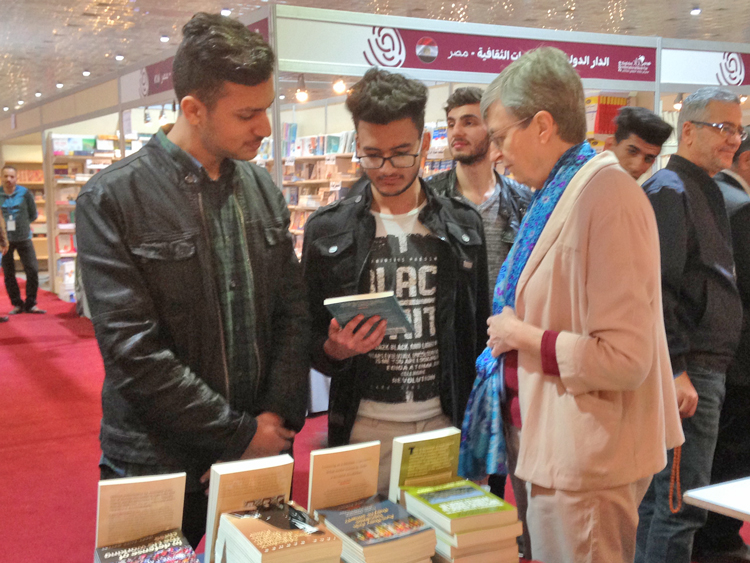 Catharina Tirsén discusses books by Socialist Workers Party leaders with Iraqi youth at Baghdad book fair Feb. 7. Event attracted thousands seeking reading after years of wars and repression.
