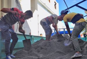 Top, student volunteers join construction workers mixing cement Feb. 2, part of efforts to repair polyclinic damaged by tornado in Havana's Diez de Octubre district. Below, string quartet plays in Diez de Octubre in Havana. It was one of many musical groups, artists, clowns and magicians who have performed in the storm-ravaged neighborhood in solidarity with working people there.