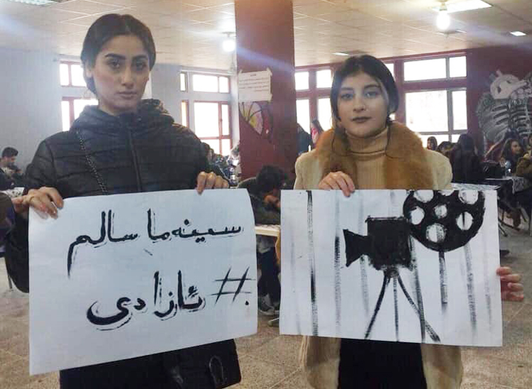 """Students at Institute of Fine Arts in Sulaymaniyah, in Kurdistan region in Iraq, joined Cinema Salim to protest censorship barring showing of film about government attacks against Kurdish struggle for self-determination in Turkey. Placard says, """"Freedom for Cinema Salim."""""""