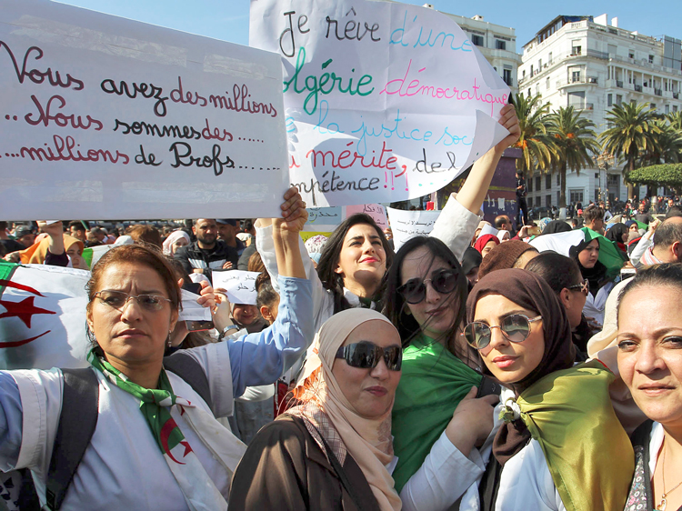 "Teachers hold placards outside Algiers post office March 13, reading at left, ""You have millions. We are millions of teachers"" and in center, ""I dream of a democratic Algeria."""