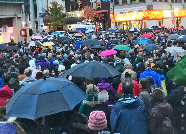 Overflow crowd at Pittsburgh vigil Oct. 27, 2018, after murder of 11 Jews at synagogue there. Inset, Rabbi Alexander Davis speaks at rally at Dar Al Farooq Islamic Center, Bloomington, Minnesota, Aug. 8, 2017, following bombing of mosque. Many Somali workers in that area say they recall the support they got from Jews there and oppose Rep. Ilhan Omar's recent anti-Semitic slanders.