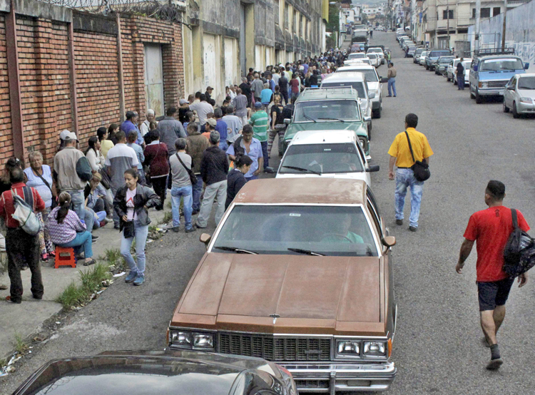People wait on long lines outside store while motorists also wait to get fuel in San Cristóbal, Venezuela, Nov. 10. Working people face shortages in food, medicine, other necessities.