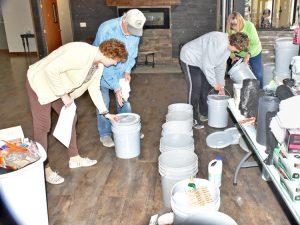Voluntarios en McCook, Nebraska, se organizan para llenar cubetas con víveres para enviar a áreas afectadas por inundaciones. El gobierno ha dejado abandonados a los damnificados.