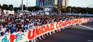 """Hundreds of thousands of people march during May Day rally in Havana to protest U.S. threats. Banner says, """"Unity, Commitment and Victory."""""""