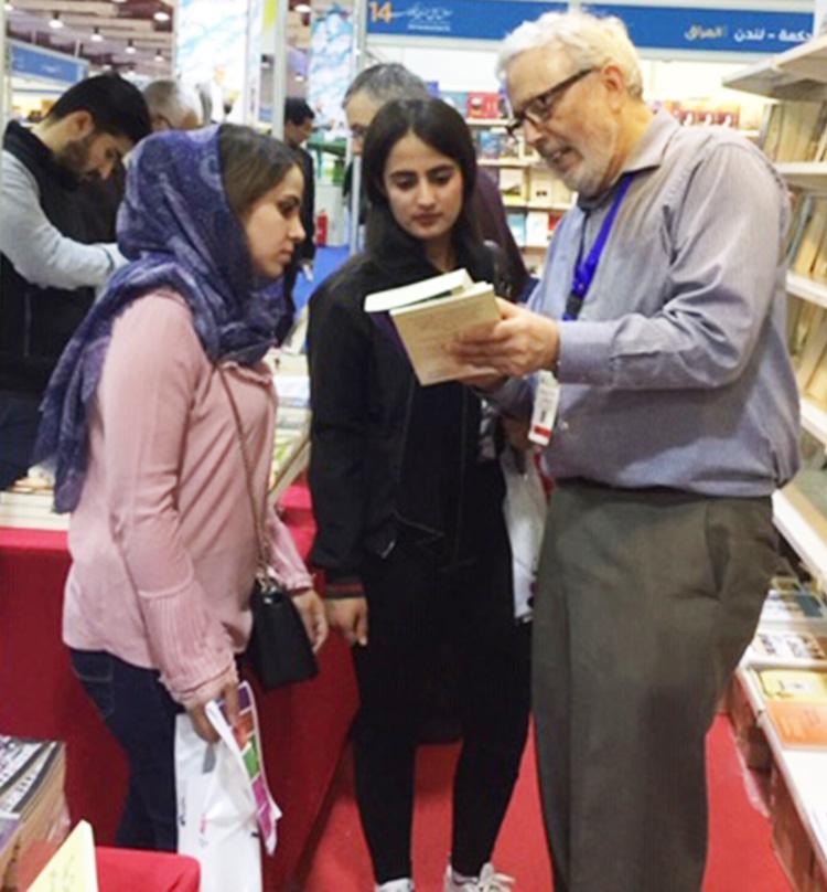 Arriba, Ögmundur Jónsson y Martin Hill (izq.) del Reino Unido en stand de Pathfinder con Mohammed Ja'far, quien está reconstruyendo biblioteca destruida por Estado Islámico en villa cerca de Mosul. Abajo, Steve Penner de Canadá muestra libros de Pathfinder.