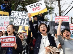 "Rally in Seoul April 11 celebrates South Korea's high court ruling that country's ban on abortion is unconstitutional. Signs say, ""Abortion law should be abolished"" and ""is unconstitutional."""
