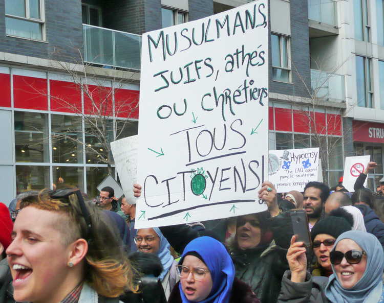 "Sign reads, ""Muslims, Jews, atheists or Christians. All citizens!"" Thousands protest in Montreal April 7 against bill banning public sector workers from wearing religious symbols at work."