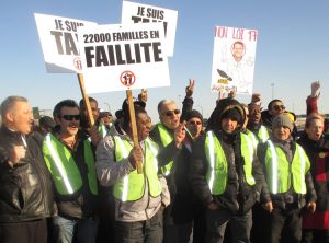 "Montreal taxi drivers protest government deregulation bill April 5. Placard says, ""22,000 families in bankruptcy."" Uber, taxi drivers need union to fight moves to pit them against each other."