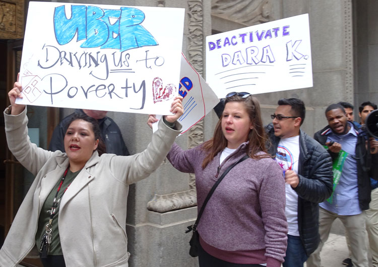 "Uber, Lyft drivers picket City Hall in Chicago May 8. Sign refers to Dara Khosrow-shahi, Uber CEO. ""We need to stand together,"" Nnamdi Uwazie of Cab Drivers United told protesters."