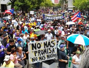 "May 1 union protest in San Juan, Puerto Rico. Front placard says, ""No more Promesa"" — the U.S.-imposed law demanding Puerto Rico pay its foreign debt — and ""No more lies."""