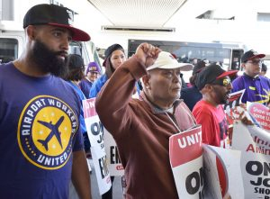 "Chanting ""One job should be enough!"" airport workers as well as Sky Chef and Gate Gourmet workers picket together at San Francisco International Airport for higher wages, new contracts."