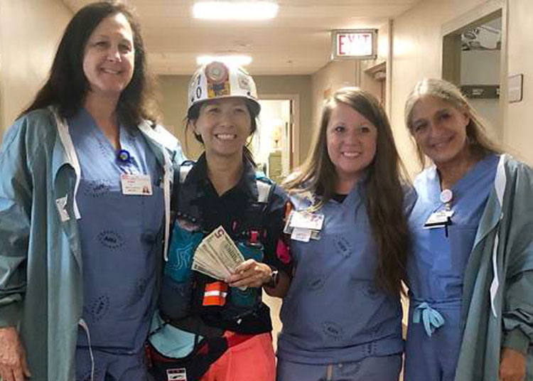 "Chinese restaurant owner Joyce Cheng, in miner's helmet and jacket, with nurses at Harlan Appalachian Regional Healthcare July 11. She ran 50 miles ""asking every person for a dollar"" for laid-off Blackjewel miners, raising over $5,000 for miners' families she knows."