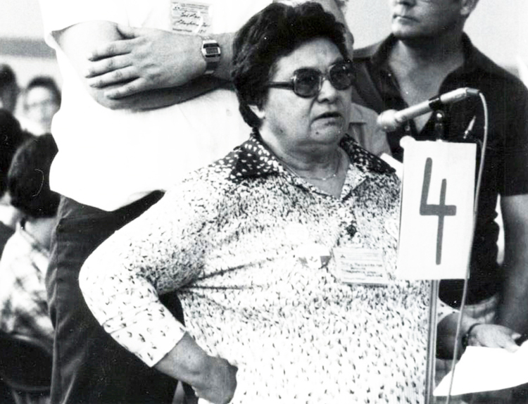Joyce Meissenheimer speaks at 1980 British Columbia New Democratic Party convention, wearing button defending Pratt Three, three women workers fired by Pratt & Whitney aerospace factory after Canadian rulers' political police told bosses they were communists.
