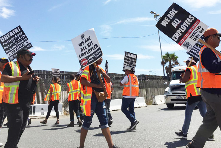 "Truck drivers employed by NFI Industries' California Cartage picket port in Wilmington, California, Sept. 9 during weeklong strike, demand to be treated as workers, not ""contractors."""