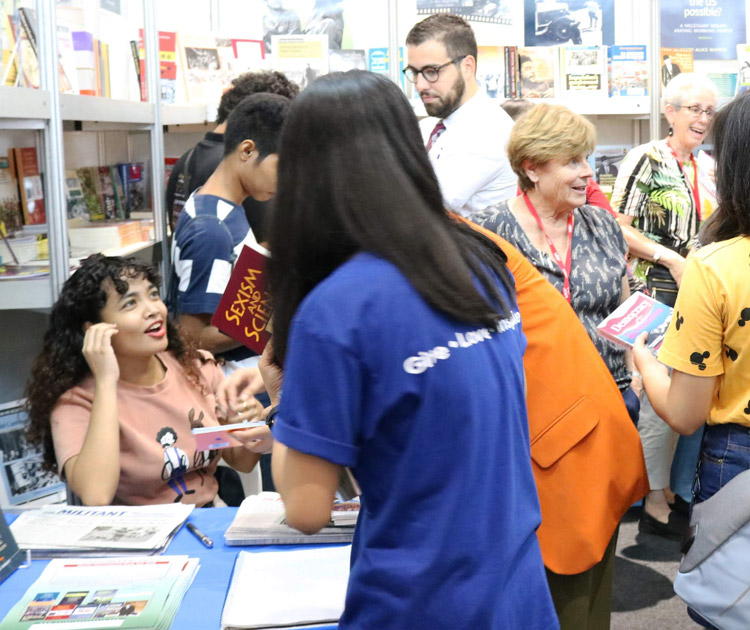 Interested youth discuss, buy literature in Pathfinder booth at Manila book fair Sept. 14, following meeting presenting Are They Rich Because They're Smart? Class, Privilege, and Learning Under Capitalism, and Women in Cuba: The Making of a Revolution Within the Revolution.