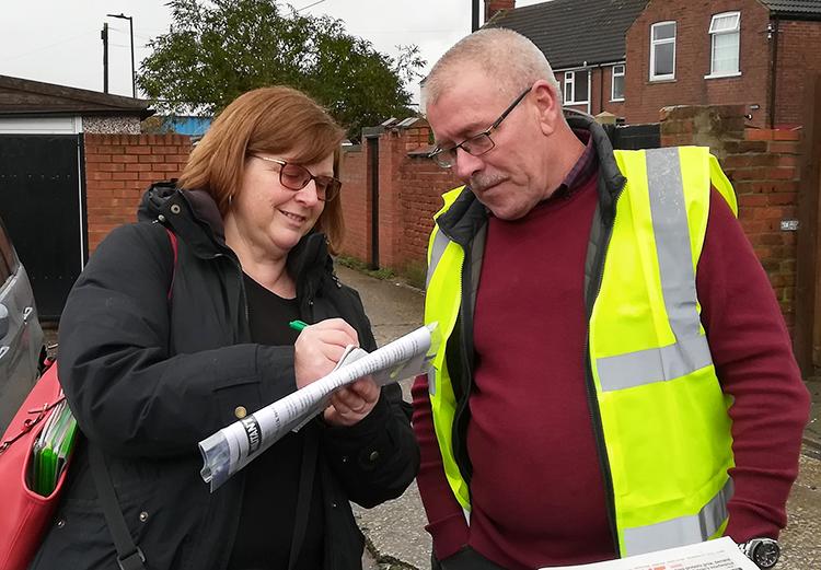 Caroline Bellamy, U.K. Communist League parliamentary candidate in Manchester, speaks with Steve Miller in Bentley Nov. 16. Miller is organizing workers into flood relief efforts.