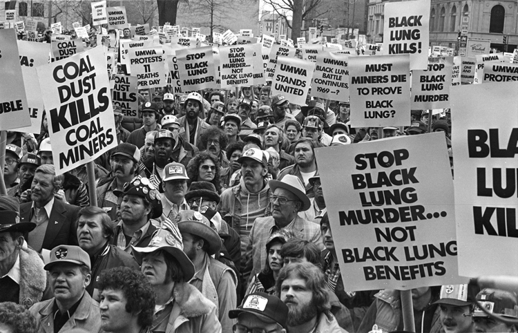 Top, miners block rails, Harlan County, Kentucky, July 2019, to stop Blackjewel bosses from hauling coal until wages owed them were paid. The nonunion miners won broad support and, in October, their back pay. Above, miners hold national protest in Washington, D.C., March 1981, a few weeks before 160,000 began 10-week strike, turning back concession contract demanded by mine bosses.