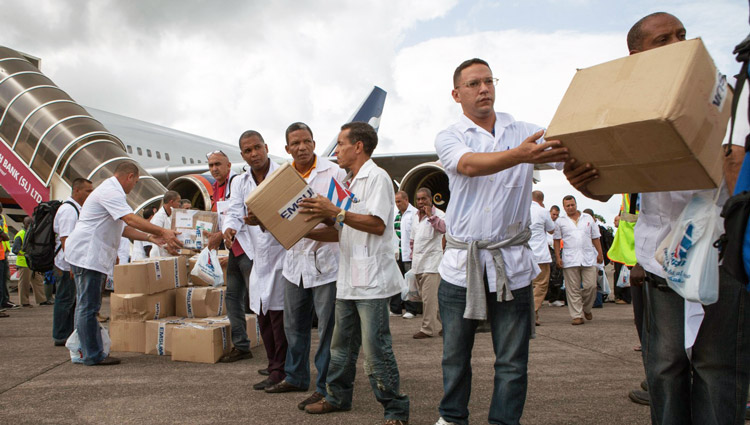 Cuban medical volunteers unload supplies on arrival in Freetown, Sierra Leone, Oct. 2014.