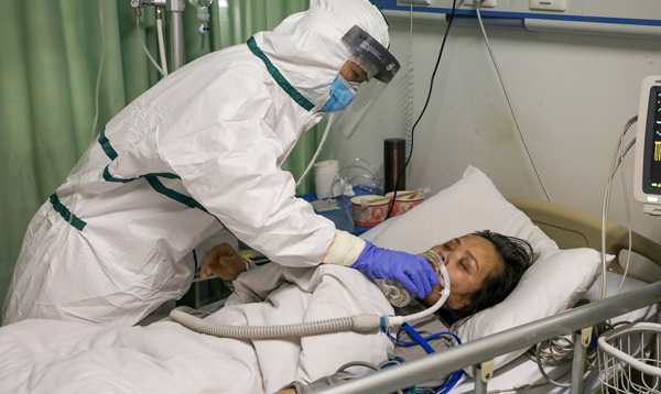 """Nurse attends coronavirus patient in Wuhan, central China, Feb. 6. Chinese government admits responsibil-ity for """"shortcomings, deficiencies."""" Seven medical workers have died so far."""