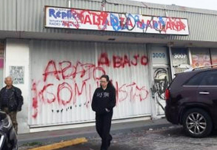 """Storefront of Alianza Martiana, a Miami organization that defends the Cuban Revolution, after attack by rightists Jan. 26. Vandals painted threat, """"Abajo comunistas"""" (Down with communists)."""